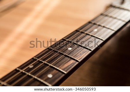 guitar neck with string on blurred wood background light and shadow filter tone