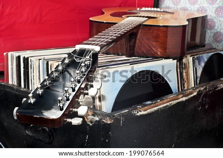 Guitar on a trunk full of old vinyl records - stock photo