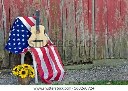 guitar on an american flag with sunflowers in basket by old barn - stock photo