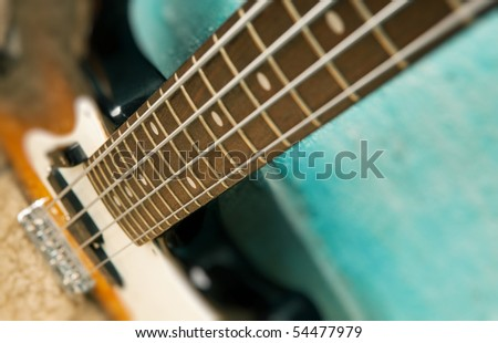 Guitar on blue background, bass on grunge wall - stock photo