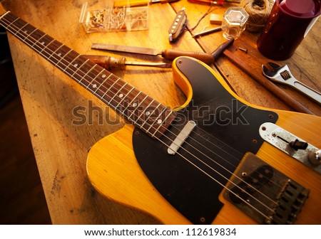 Guitar on guitar repair desk. Vintage electric guitar on a guitar repair  work shop. Single cutaway solid body guitar, amber color. Warm lighting - stock photo