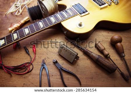 Guitar on guitar repair desk. Vintage electric guitar on a guitar repair work shop. Single cutaway solid body guitar, gold color. - stock photo