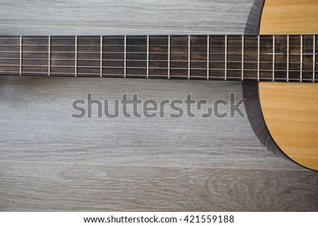 Guitar on wooden background, fretboard, musical instrument, fretboard, stringed musical instruments, guitar details close up, solo instrument, blues, country, flamenco, rock, metal, jazz     - stock photo