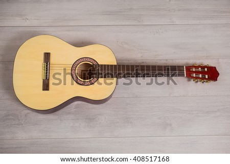 Guitar on wooden background, fretboard, stringed musical instruments, guitar details, solo instrument, blues, country, flamenco, rock, metal, jazz - stock photo