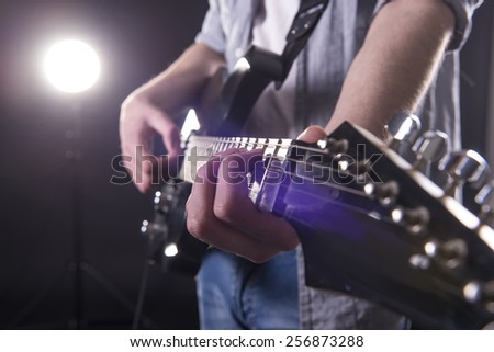 Guitar player. Close-up hands of young man is playing guitar in dark room with lights behind him. - stock photo