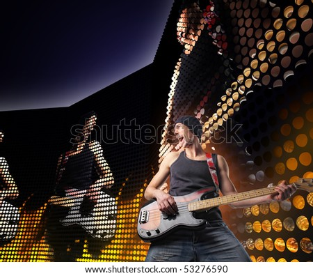 guitar player on concert with huge led screen background - stock photo