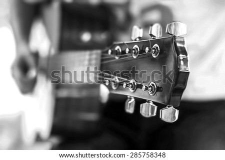 Guitar player playing song outdoor, Black and White - stock photo