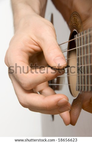 Guitar player's right hand picking a classical guitar