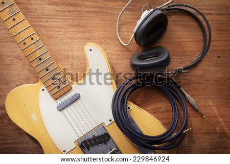 Guitar recording. An electric guitar, and a professional use headphones on a rustic or bare wooden table, with by-the-window type warm light coming in.  - stock photo