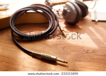 Guitar recording. An electric guitar, and a professional use headphones on a rustic or bare wooden table, by the window.  - stock photo