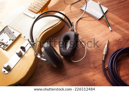 Guitar recording scene. An electric guitar, memo pad , and a professional grade headphones on a rustic or bare wooden table, with by-the-window type warm light coming in. - stock photo