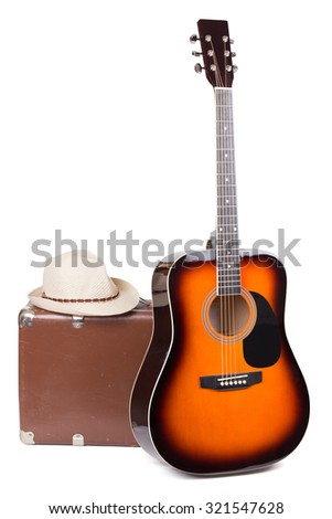 guitar with an old suitcase and a hat over white