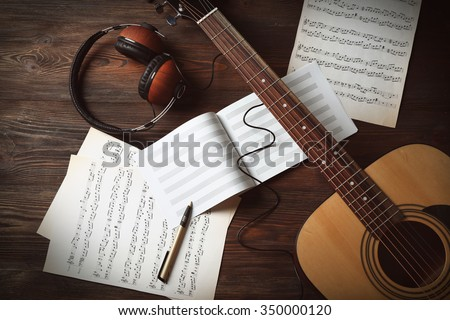 Guitar with earphones and music sheets on wooden background - stock photo