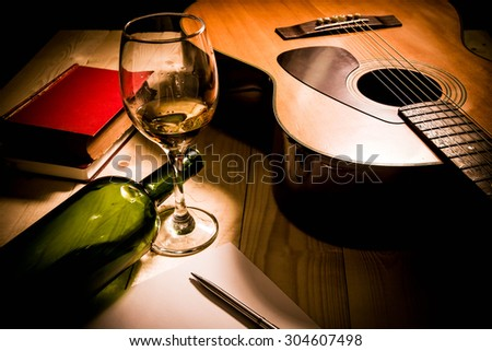 Guitar with Red Book and Wine on a wooden table. - stock photo