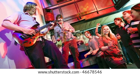 Guitarist and saxophone player, accompanied by a DJ, during a gig with an enthusiastic crowd in a discotheque - stock photo