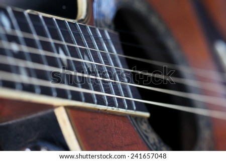 Guitarist hand play guitar on concert stage with blue light, Practicing music instrument.