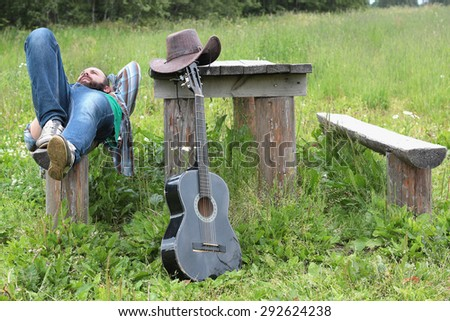 guitarist in a cowboy hat on the nature