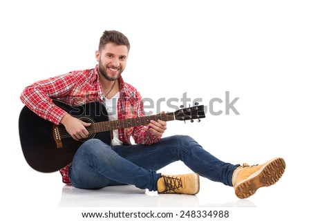 Guitarist in red lumberjack shirt sitting on a floor and play the black acoustic guitar. Full length studio shot isolated on white. - stock photo