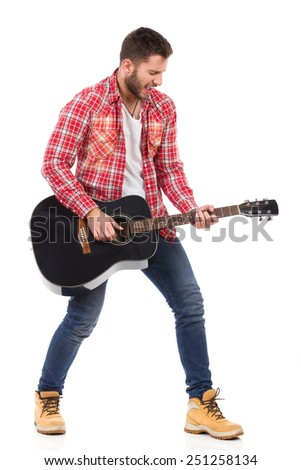 Guitarist in red lumberjack shirt standing with legs apart and play the black acoustic guitar. Full length studio shot isolated on white. - stock photo