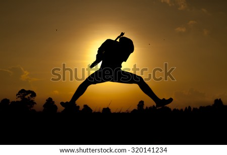 Guitarist jumping Playing Rock Music Against - stock photo