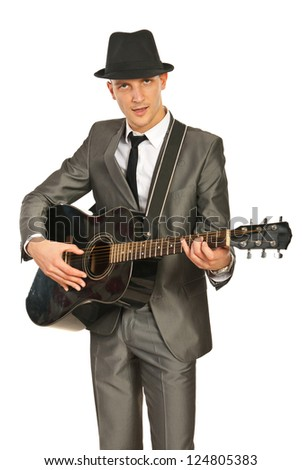 Guitarist man in elegant suit and hat playing guitar isolated on white background