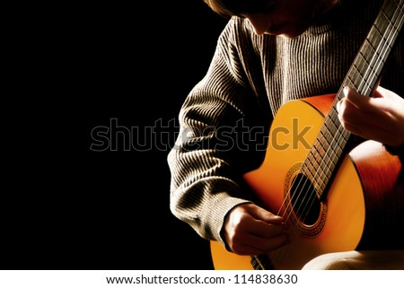 Guitarist musician guitar acoustic playing. Young man performer on black background - stock photo