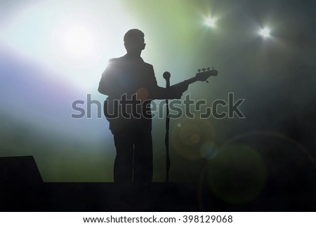 Guitarist on stage performing live under spotlight - stock photo