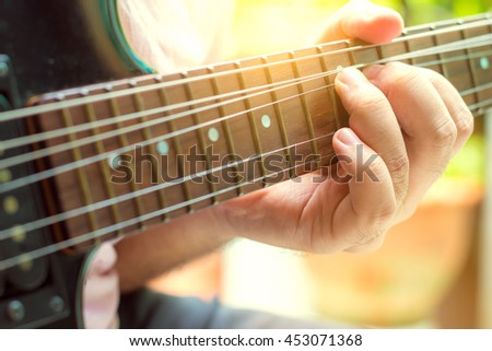Guitarist playing an electric guitar. Shallow depth of field.