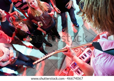 Guitarist playing in a crowded nightclub, with fans partying around the stage - stock photo