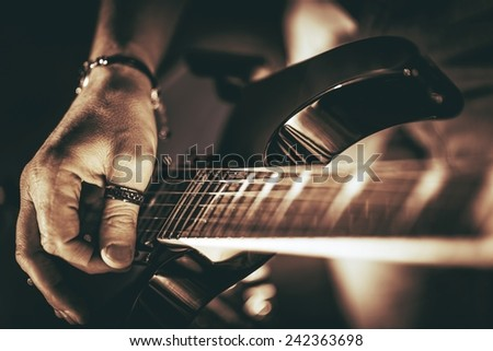 Guitarist Plays. Electric Guitar Playing Closeup Photo. Rockman Guitar Player Music Theme. - stock photo