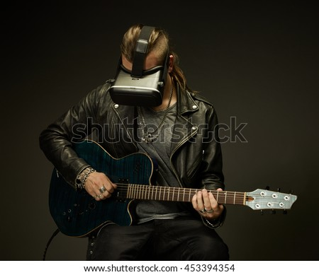 Guitarist plays guitar in a virtual reality glasses.