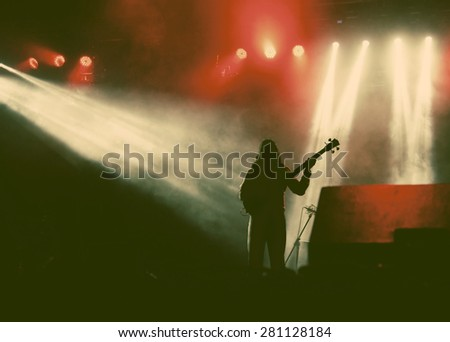 Guitarist silhouette in smoke during concert  - retro style photograph - stock photo