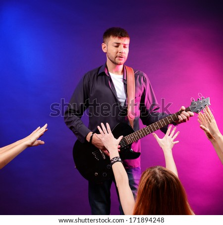 Guitarist singing on stage at a rock concert for his adoring fans - stock photo
