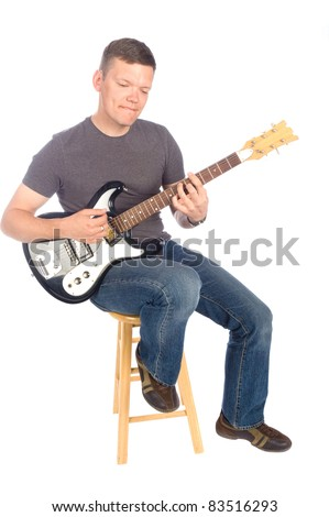 Guitarist sitting on stool playing his guitar isolated on a white background