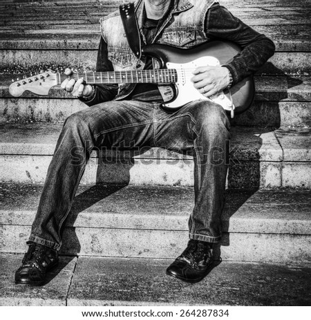 guitarist with a colorful guitar in hdr tone mapping effect. Black and white. - stock photo