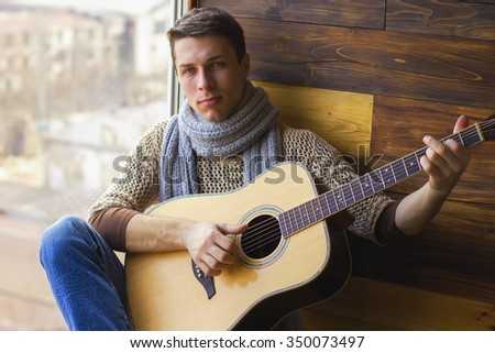 guitarist young guy in jeans with a guitar sitting in the window fuzzy focus