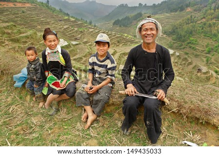 GUIZHOU, CHINA - APRIL 10: Ethnic Minorities in China, Miao black family on the background of the mountain landscape in the rice terraces in the spring, April 10, 2010. Basha Village, Congjiang County