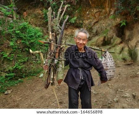 GUIZHOU PROVINCE, CHINA - APRIL 11: An elderly Chinese man goes on mountain road with load on yoke, carries nylon bag and an armful of branches for  hearth, Zengchong village,  - April 11, 2010. - stock photo