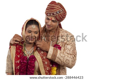 Gujarati groom tying a mangal sutra around brides neck