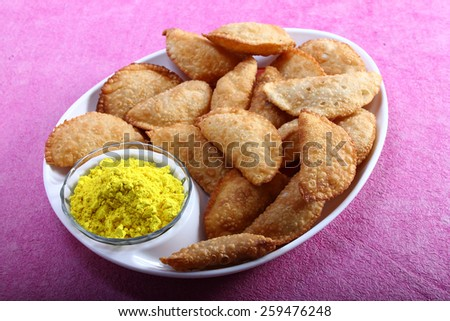 gujia, indian traditional snacks for holi festival with yellow color in bowl