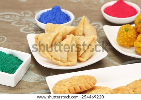 Gujiya and other Indian Sweets with Gulal or Face Powder at Holi - stock photo
