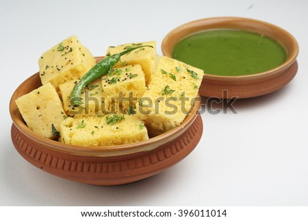 Gujrati khaman Dhokla in terracotta bowl, top angle isolated over white background - stock photo