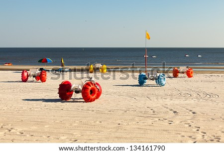 Gulf coast beach in Biloxi, Mississippi with water tricycles and lounge chairs. - stock photo