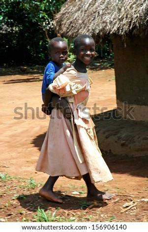 GULU, UGANDA, AFRICA - CIRCA MAY 2005:  Unidentified sister carries her baby brother on her back circa May 2005 in Uganda, Africa.