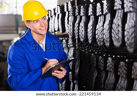 gum boots worker counting stocks and making notes in warehouse - stock photo
