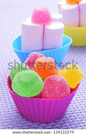 gumdrops of different colors and marshmallows in bowls of different colors on a purple woven background - stock photo