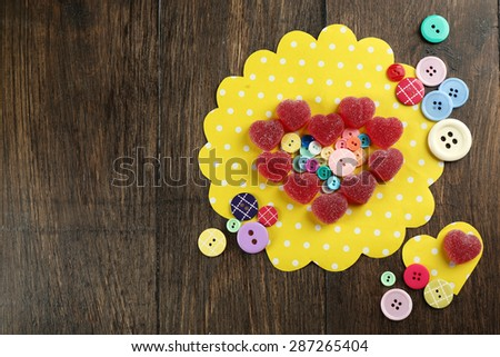 Gummy candies arranged in heart shape with buttons on table close up - stock photo