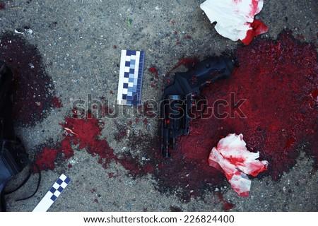 Gun and blood at crime scene  - stock photo