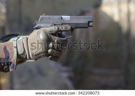gun and camouflage gloves