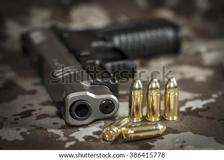 Gun and cartridges - focus on the barrel - stock photo